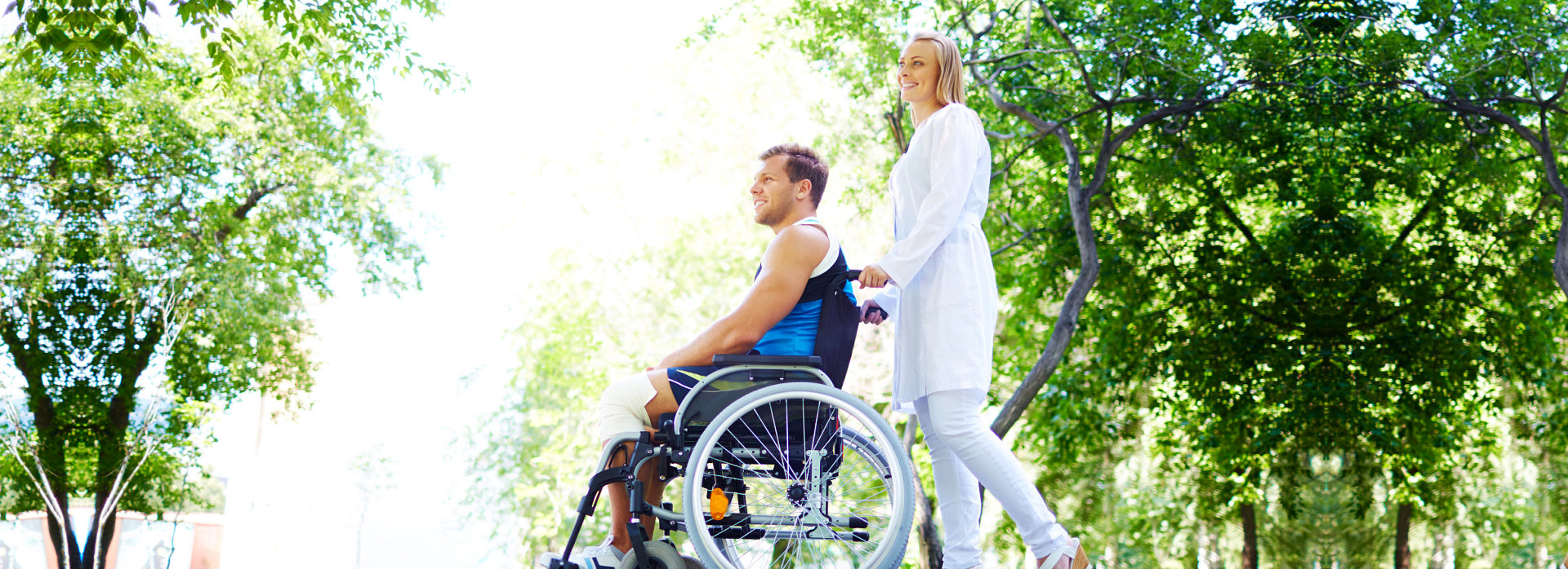 young woman in a wheelchair taking a walk in the park assisted by his caregiver